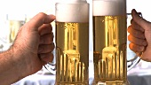 Hands clinking beer glasses