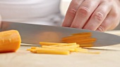 Chopping carrots into julienne strips