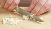 Chopping garlic cloves finely