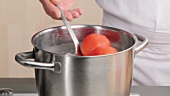 Placing tomatoes in boiling water