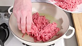 Placing minced meat into a frying pan with oil