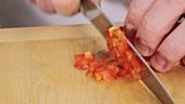 Rote Paprikaschote in feine Würfel schneiden