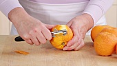 Peeling Seville oranges using a peeler
