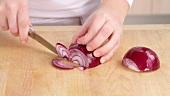 Rote Zwiebel halbieren und in halbe Ringe schneiden