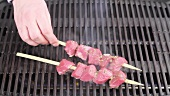 Marinated lamb kebabs being placed on a barbecue
