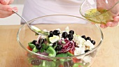 Greek salad being drizzled with vinaigrette