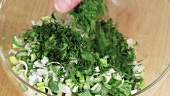 Dill being added to finely chopped spring onions