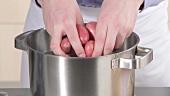 Ungeschälte Kartoffeln in einen Topf mit kaltem Wasser geben