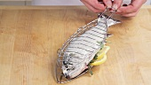 Prepared herb trout being placed in a grill basket