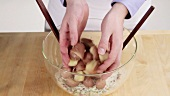 Potatoes being added to a vegetable and mayonnaise mixture