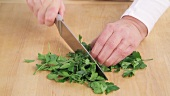 Parsley leaves being removed and chopped