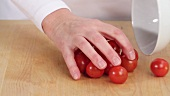Cherry tomatoes being placed on a work surface