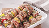 Grilled meat and vegetable kebabs being sprinkled with salt