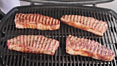 Grilled New York strip steaks being removed from a grill