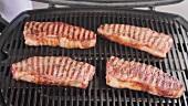 Gegrillte New York Strip Steaks vom Grill nehmen