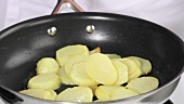 Potato slices being fried in a pan
