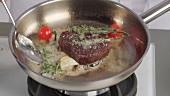 A fillet steak being season and aromatised with herbs, garlic and tomatoes