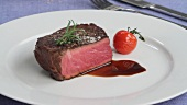 A beef fillet steak with herbs and a tomato