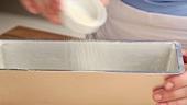 Gebutterte Kastenform mit Paniermehl ausstreuen