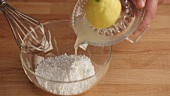 Icing sugar and lemon juice being mixed to make a glaze