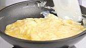 Eiermasse in einer Pfanne unter Rühren stocken lassen