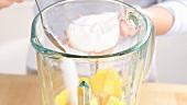 Zucker zu den Mangostücken in einem Mixer geben