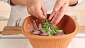 Herbs being added to vegetables in a terracotta baking dish