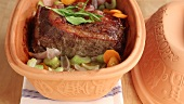 Roast beef with vegetables in a terracotta baking dish