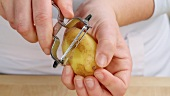A potato being peeled (close-up)