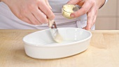 A baking dish being greased with butter