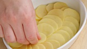Potato slices being layered into a baking dish