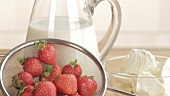 Fresh strawberries in a sieve with milk and vanilla ice cream