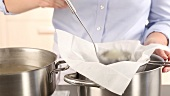 Stock being poured through a sieve lined with kitchen paper