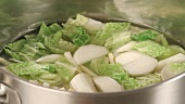 Savoy cabbage and root vegetables being cooked in stock