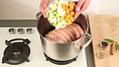 Soup vegetables being added to pork loin in a pot
