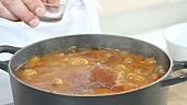 Simmering chilli con carne being seasoned
