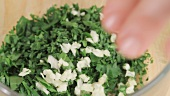 Garlic being added to finely chopped parsley