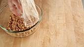 Keksbrösel in eine Glasschüssel geben