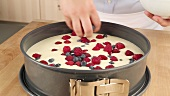 Fresh berries being sprinkled on a fridge cake