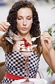 Woman pouring hot raspberries over vanilla ice cream
