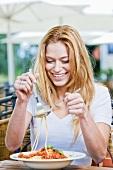 Junge Frau isst Spaghetti Bolognese