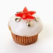 Iced muffin decorated with chocolate beans and jelly sweet