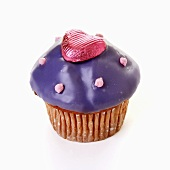Muffin with purple icing and chocolate heart