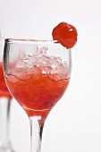 Roter Cocktail auf crushed ice mit Cocktailkirsche