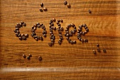 The word 'coffee' written in coffee beans on wooden background