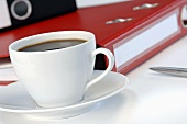 Cup of coffee in front of folders, close-up
