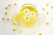 Chamomile tea in cup with flowers and lemon, close-up