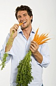 Young man eating carrots