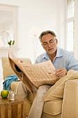 Mature man reading newspaper on sofa