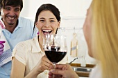 Three young people drinking wine in kitchen, smiling, close-up